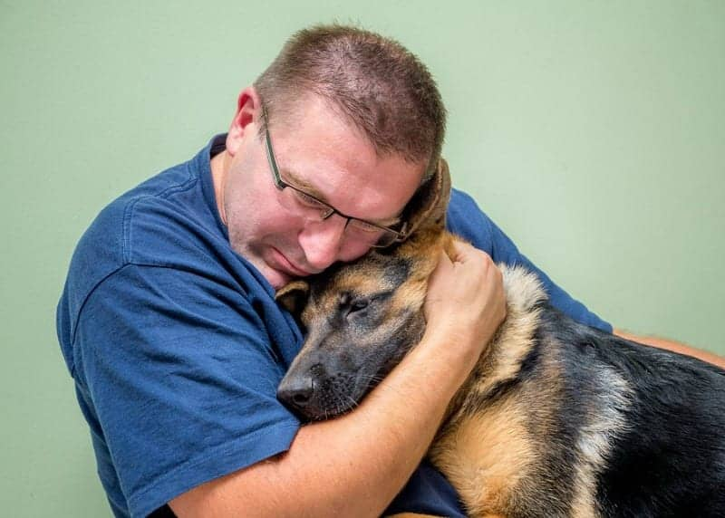 Man hugging German Shepherd Dog